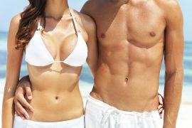 Cropped midsection of a tanned caucasian couple holding each other with the ocean in background