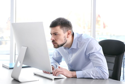 man hunched over office computer