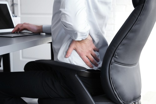 man massages hurting lower back