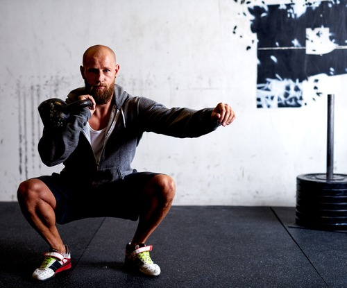 man doing squats with kettle bell
