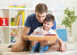 young boy reading stories with dad