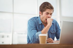 man tired at work yawning should start using Progentra