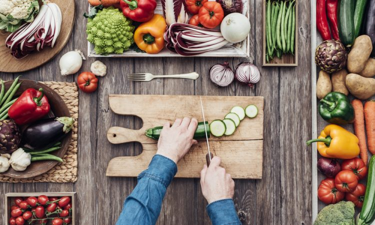man chopping vegetables prepare healthy meal to have with Progentra pills