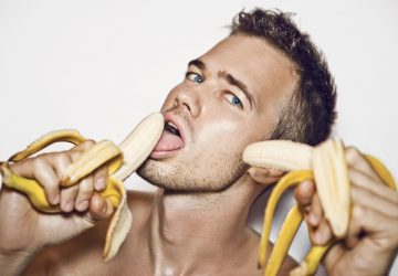 man holding and licking peeled bananas
