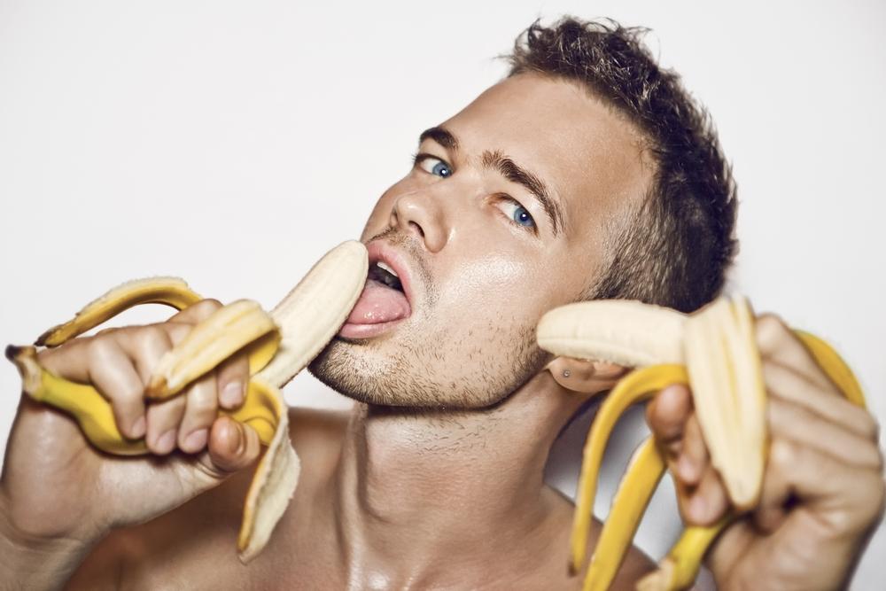 man holding and licking peeled bananas