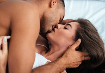 passionate couple kissing in bed
