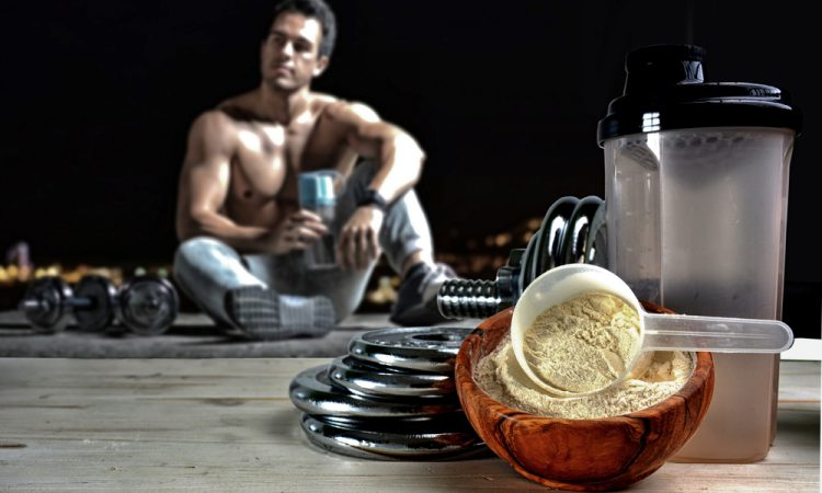Protein powder supplement with weights and sportsman in background