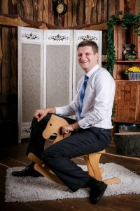 grown man playing with wooden rocking horse