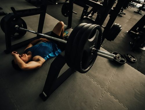 exhausted man lying on gym floor after overtraining with barbell