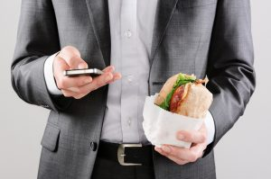 businessman on the go holding sandwich