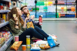 couple eating junk food in convenience store