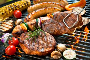 different barbecued meat and vegetable on a grill