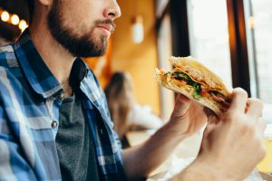 man slowly consuming his sandwich