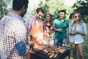 friends enjoying a barbecue party in backyard