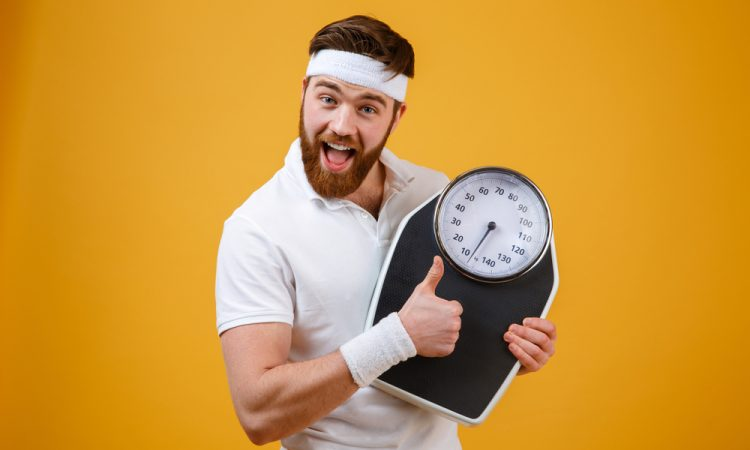 fitness guy who takes Progentra holding a scale and giving a thumbs up