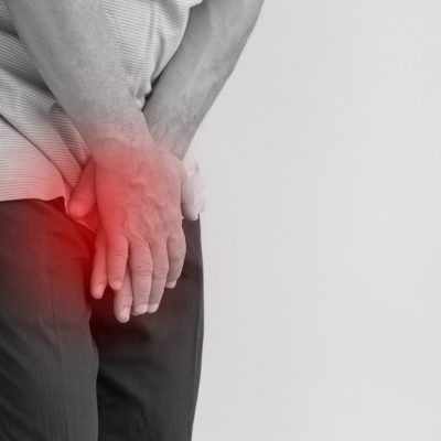 man suffering from chronic prostatitis holding his crotch